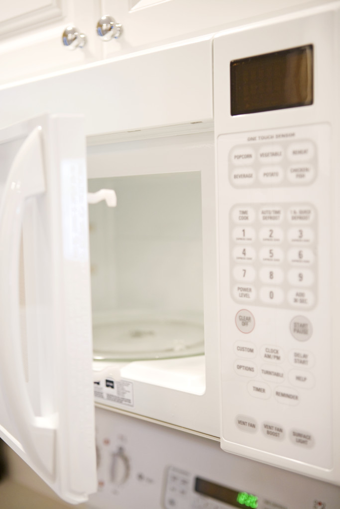 Open microwave hanging over white range